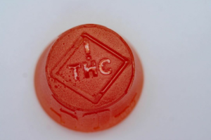 A large, red incredibles cannabis-infused medical gummy. Start low and go slow to avoid a cannabis overdose.