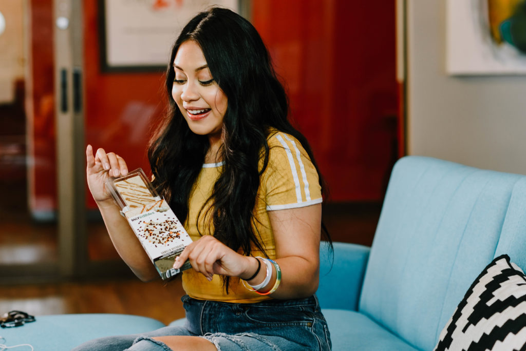 Girl with long, dark hair and bracelets wearing a short sleeved yellow shirt with white stripes on the sleeve eating an incredibles cannabis edible to relieve chronic pain