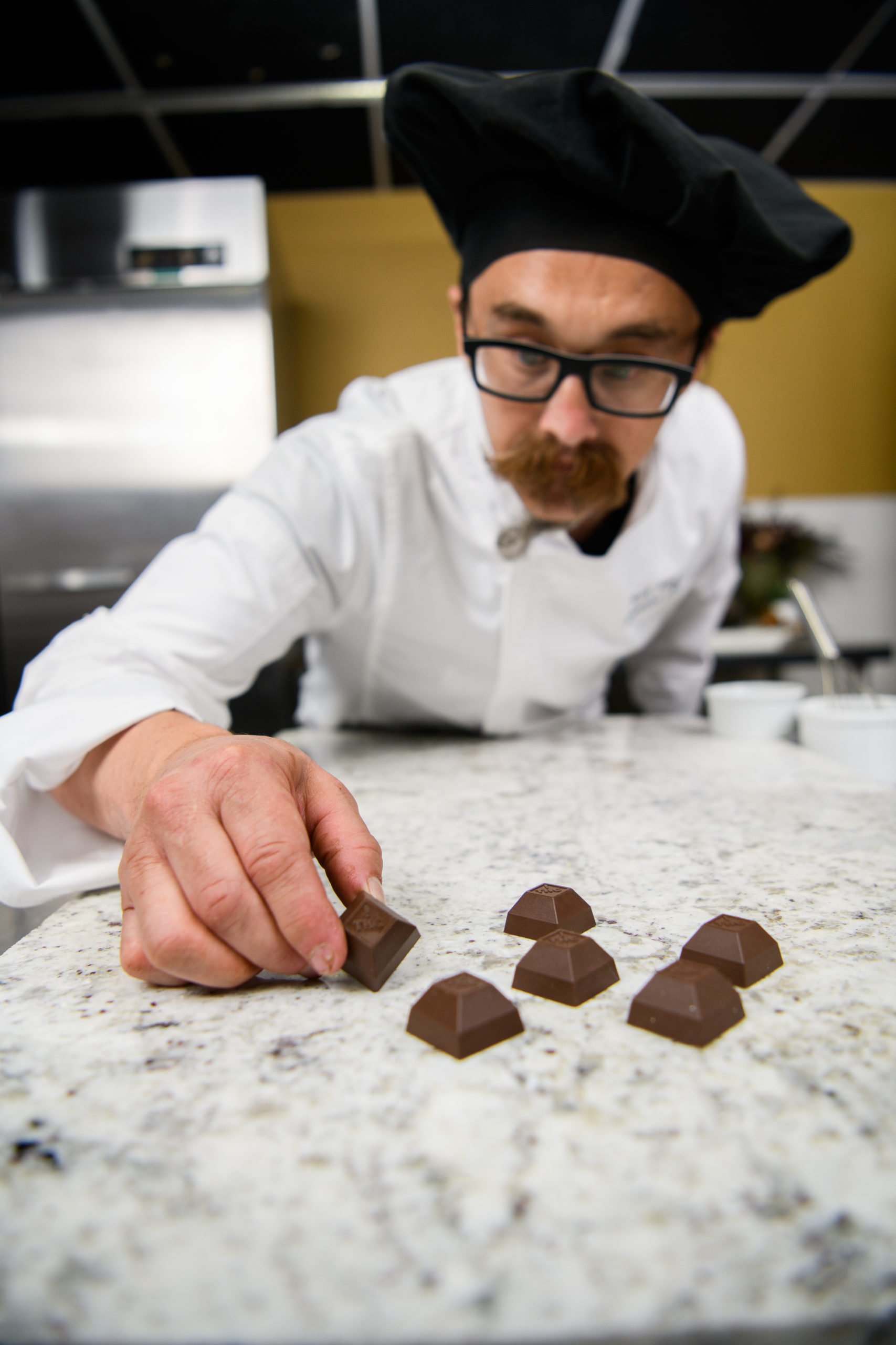 Josh Fink, Co-Founder and Executive Chef at Medically Correct, examines Nove luxury cannabis-infused chocolates.
