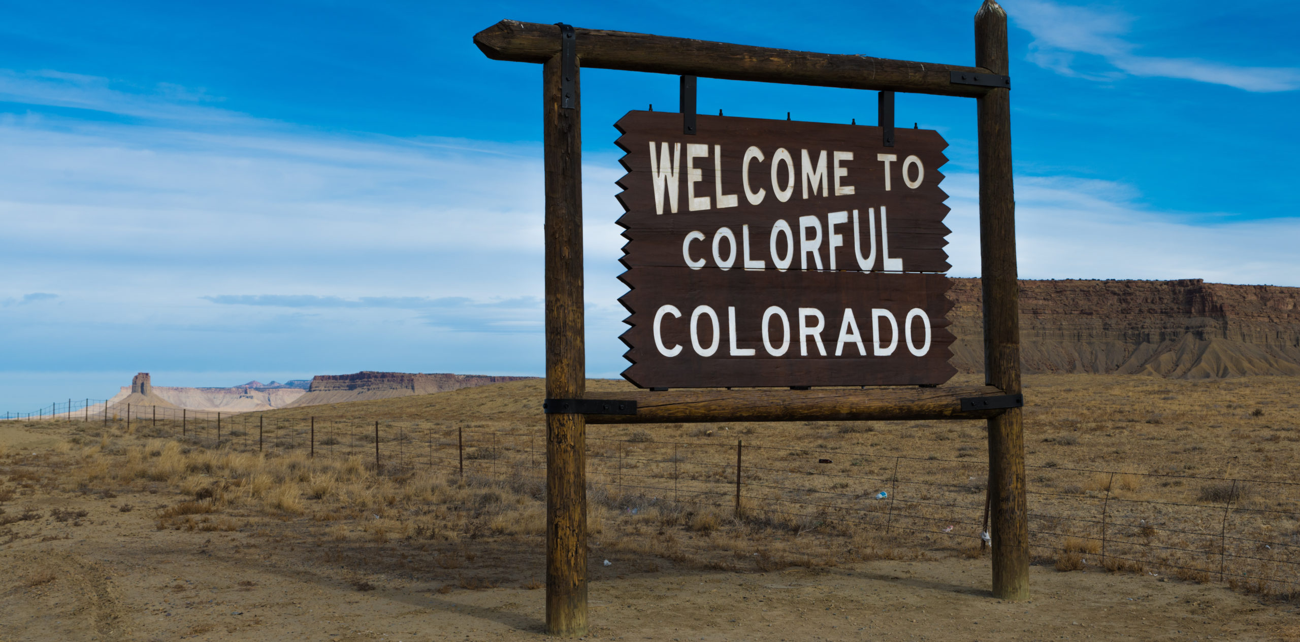 Welcome to Colorado sign wiht blue sky and mountains in the background