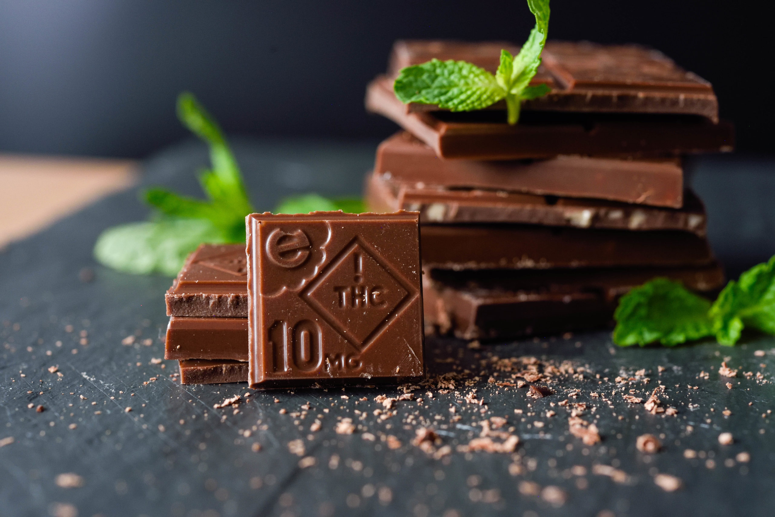 A stylized shot of incredibles cannabis-infused Mile High Mint bar, stacked and resting with mint leaves