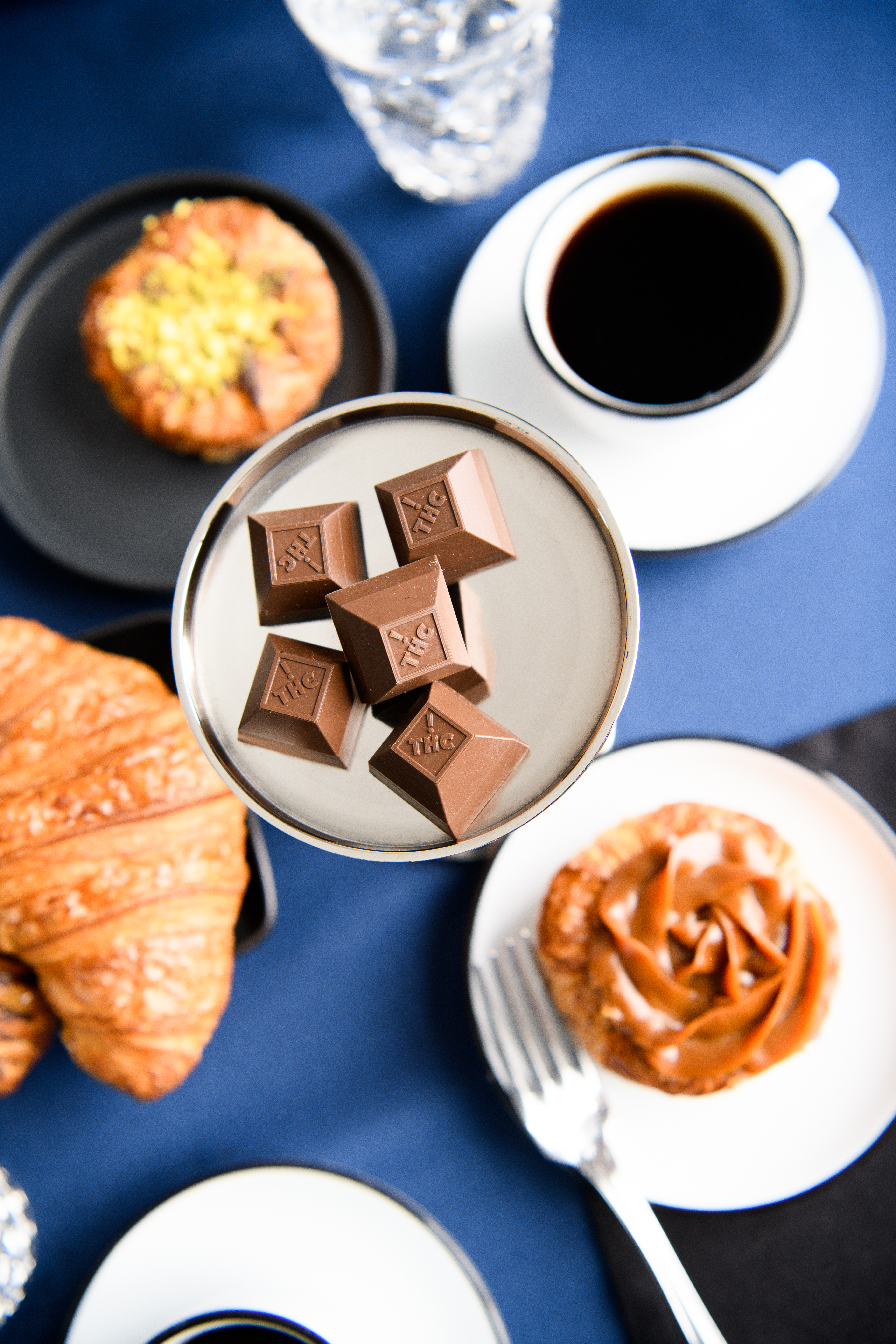 Nove cannabis-infused luxury chocolates pedestaled on a silver tray with other delicious pastries and coffees surrounding them. The blue tablecloth creates a stark contrast.