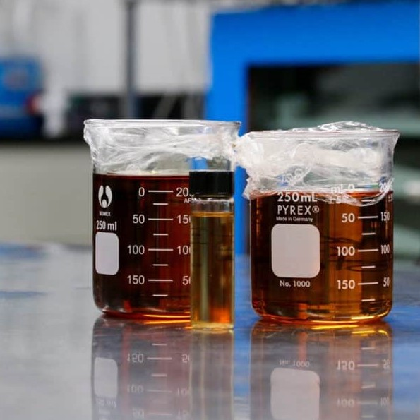 A shot of two lab beakers full of cannabis distillate extracted by Clear Creek Extracts. This oil is used in cannabis vapes.