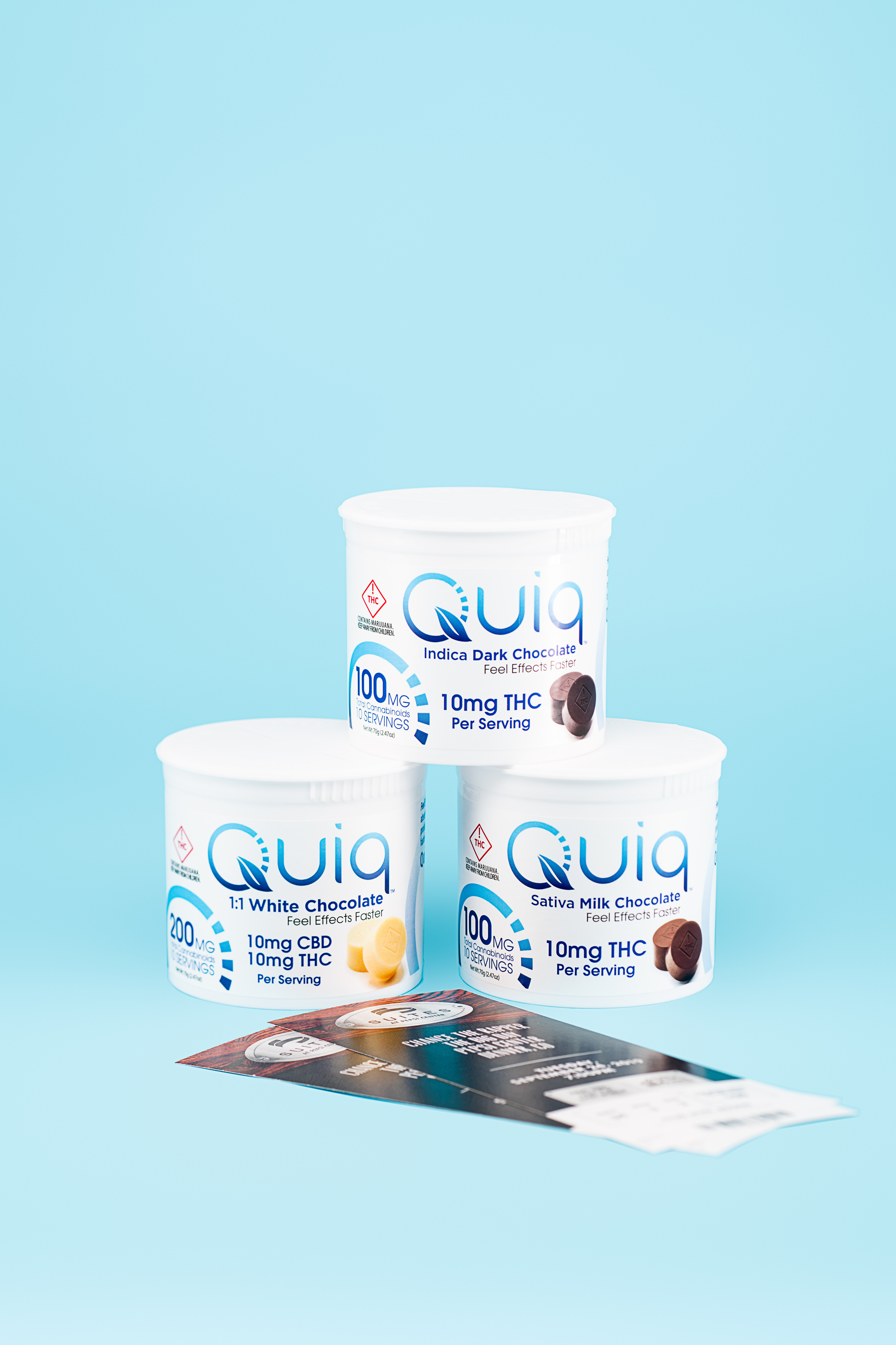 Three Quiq fast-acting cannabis chocolates are stacked in front of a blue background.