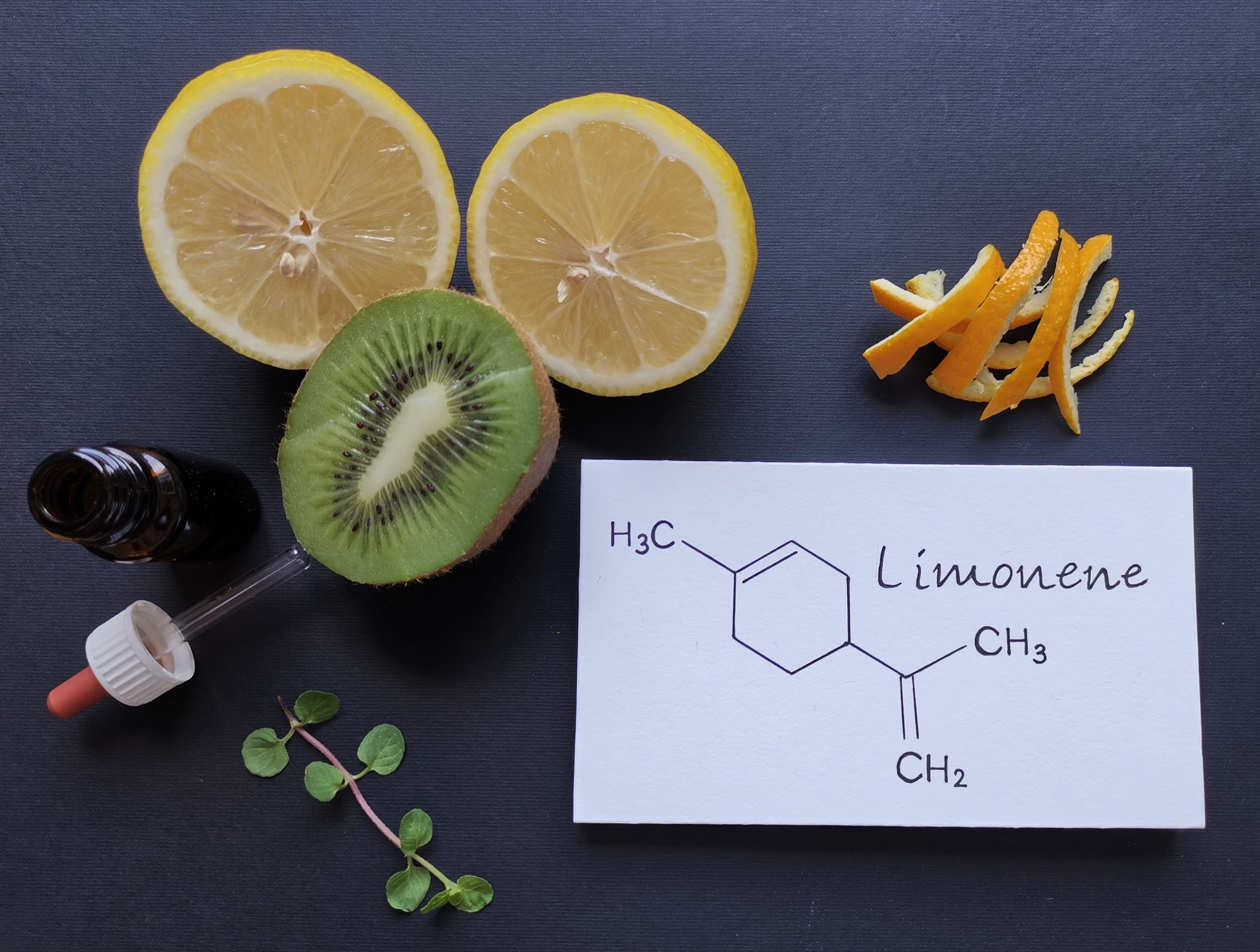 Structural chemical formula of limonene with fresh citrus fruit and a glass bottle of essential aroma oil. Limonene is the major component in the oil of citrus fruit peels. Beauty and spa products.