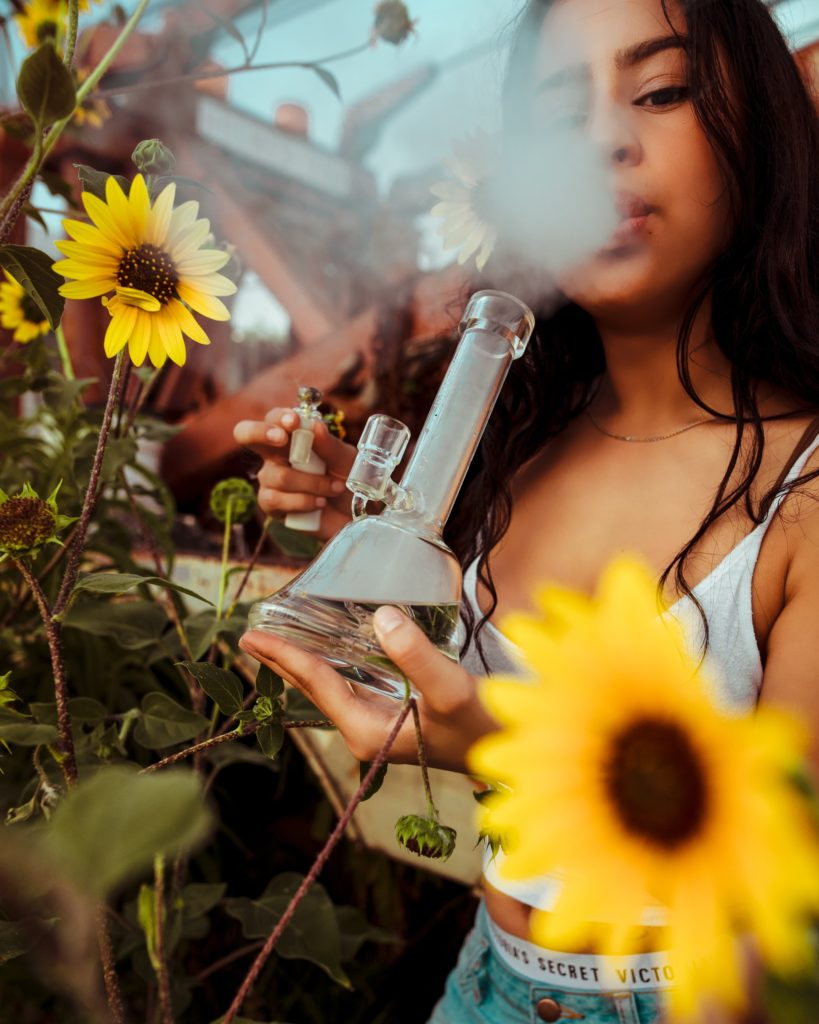 Girl with long, dark hair, a white tank top, and jean shorts holding sunflowers and a glass bong smoking cannabis outside to relieve chronic pain