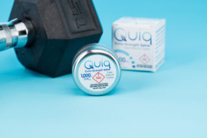Stylized shot of Quiq Extra Strength Salve against a blue backdrop