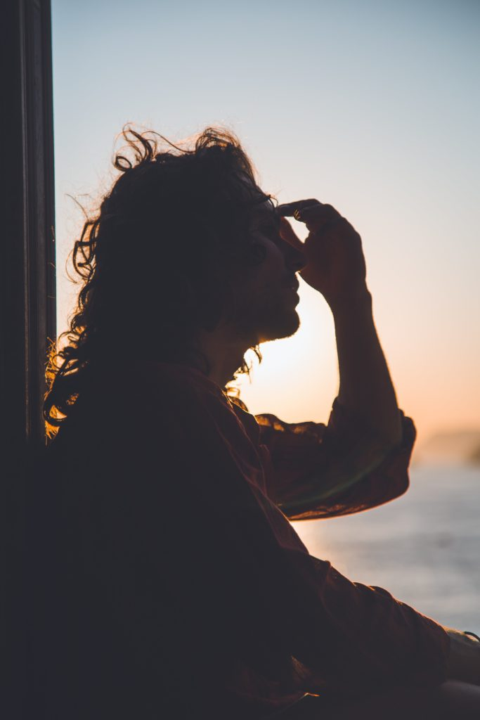 Shadowy person at sunset, looking outdoors after consuming cannabis for anxiety