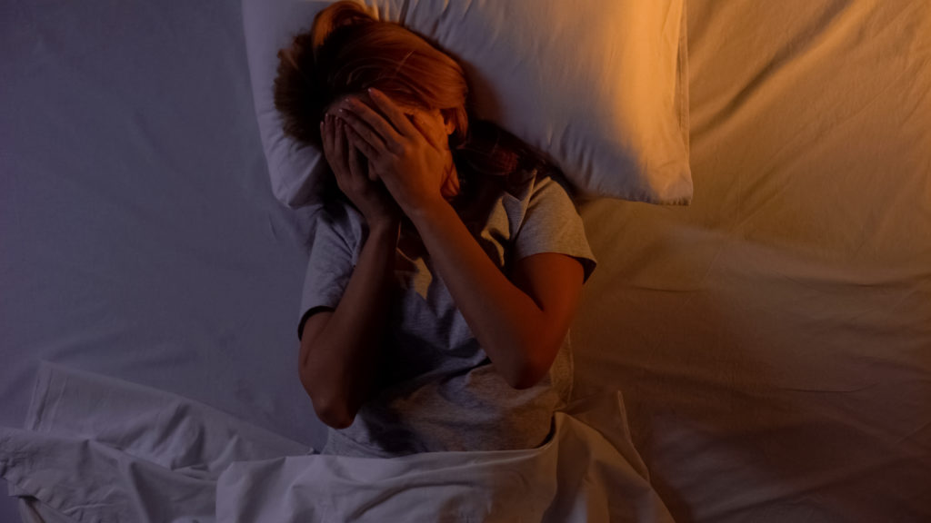 Woman struggles to sleep at night. What does science say about using cannabis for better sleep?