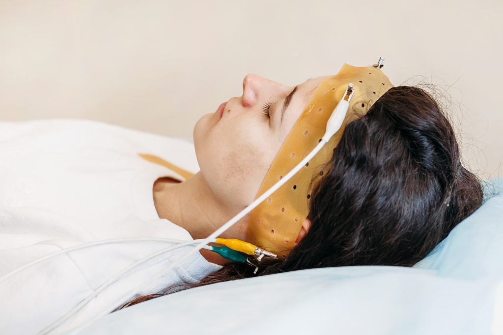 Young woman wearing the brainwave scanning headset sits in a chair. She is participating in a research sleep study.