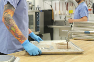 A woman dispensing infused cannabis chocolate into molds in the Medically Correct (incredibles) kitchen.