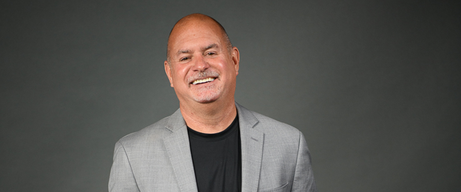 Bob Eschino, Medically Correct President and Co-Founder, dressed in a grey suit for a headshot.