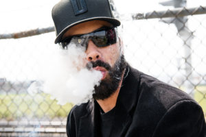 Derek Cumings, Co-Founder of Medically Correct, exhaling a cloud of smoke after toking a blunt.