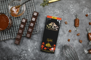 Nove Sea Salt Caramel luxury cannabis chocolates resting on a slate surface with kitchen utensils. The new line is hand crafted by Medically Correct's Co-Founder and Executive Chef, Josh Fink.