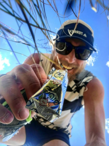 Ultrarunner athlete Avery Collins picking up a piece of Quiq cannabis chocolates.