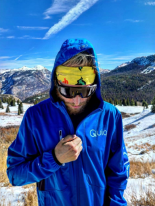 Ultrarunner Avery Collins zipping up a Quiq cannabis-branded coat.