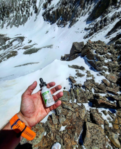 An athlete holding a bottle of trupura CBD tincture on a Colorado mountaintop.